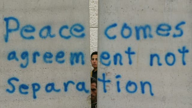 """Zwei Jungen schauen hinter einer Mauer hervor auf der steht: """"Peace comes agreement not Separation"""""""