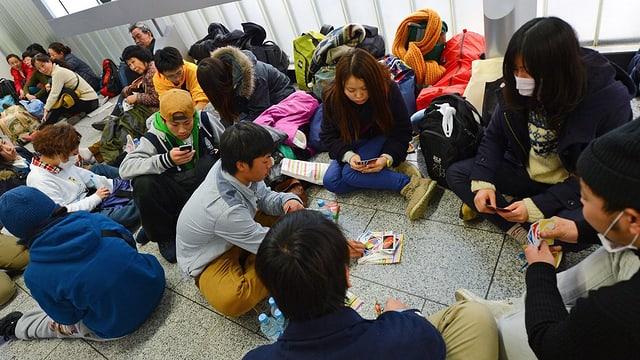 Eine Gruppe asiatischer Jugendlicher vertreibt sich die Zeit mit einem Kartenspiel.