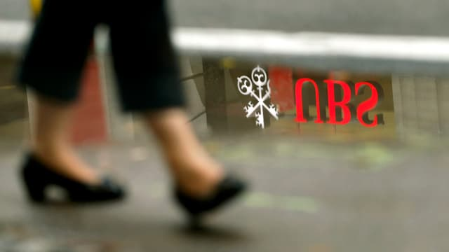 Eine an einer Pfütze vorbeigehende Frau, in der Pfütze spiegelt sich das UBS-Logo.