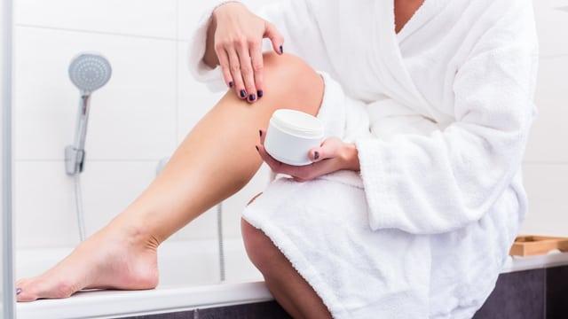 Frau cremt sich ihr Bein ein