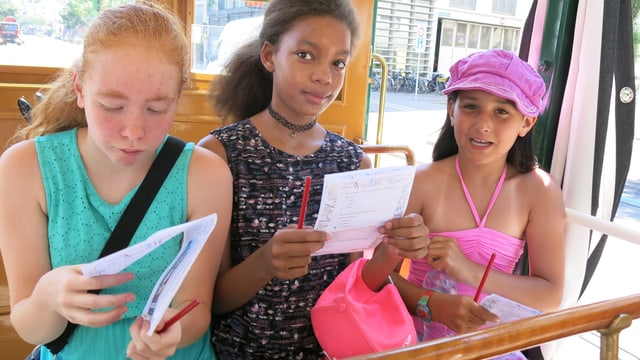 Drei Mädchen sitzen in einem offenen Tramwagen mit Bleistift und Fragebogen. Sie versucehn die Fragen zu beantworten.