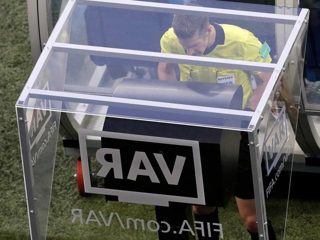 Ein Schiedsrichter schaut sich am TV eine strittige Szene an.