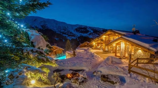 Beleuchtete Villa bei Nacht.