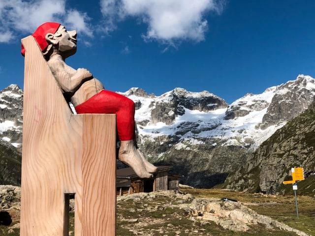Eine Puppe hockt auf einen überdimensionalen Stuhl, dahinter die Bündner Berge.