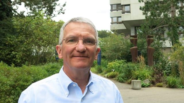 Portraitbild von CEO Ulmann, im Hintergrund das 1974 gebaute Hauptgebäude