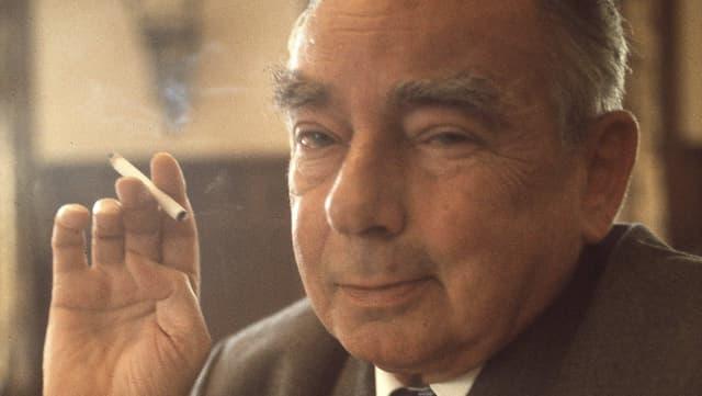 Erich Kästner mit einer brennenden Zigarette in der Hand schaut lächelnd in die Kamera