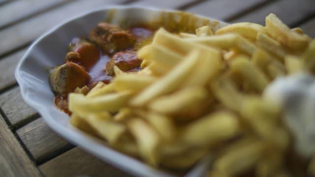 Eine Portion Currywurst mit Pommes Frites.