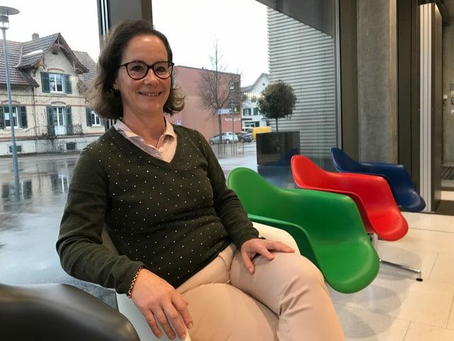 Frau sitzt auf farbigem Stuhl