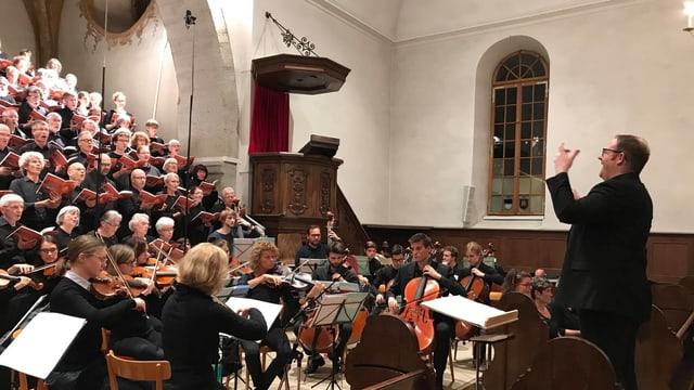 Ein Chor im Hintergrund. Im Vordergrund das Orchester.