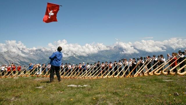 Menschen mit Alphorn und Schweiz-Fahne.
