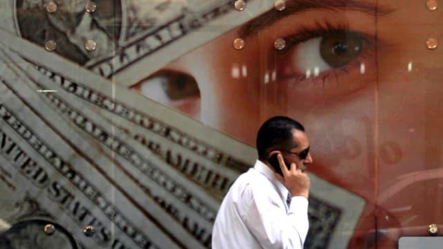Ein Mann in einem weissen Hemd und mit Sonnenbrille telefoniert vor einem Plakat mit Dollars und Frauenaugen.