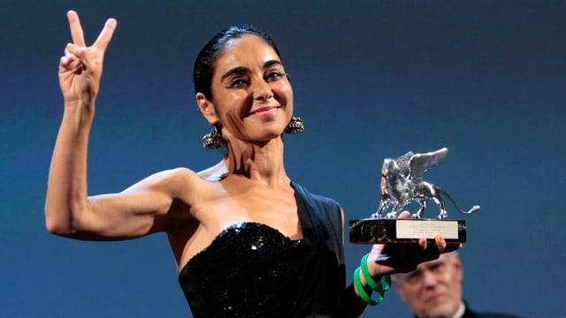Eine Frau hält stolz eine Trophäe in die Luft.