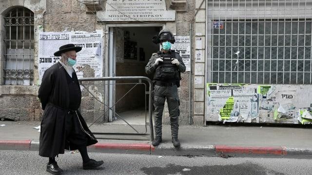 Jüdisch gekleidete Person mit Schutzmaske und israelischer Soldat.