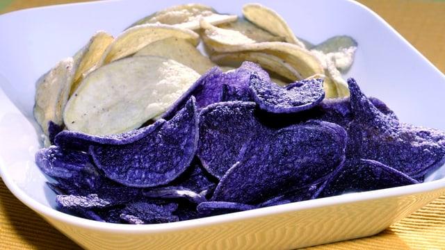 Ein Teller mit Pommes-Chips, die hälfte von ihnen ist blau.