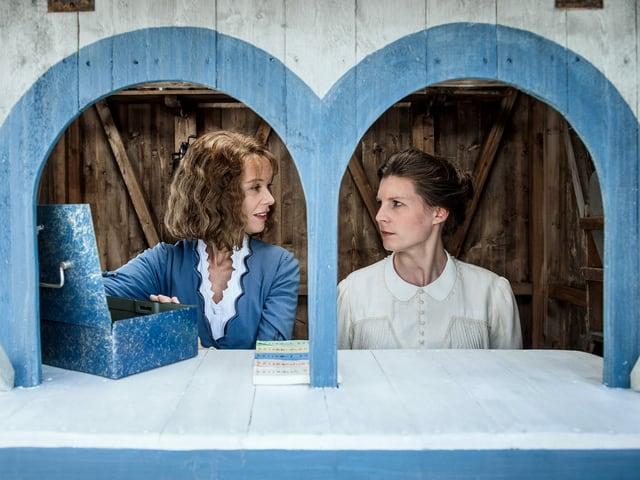 Zwei Frauen sitzen in einem Kassenhäuschen.