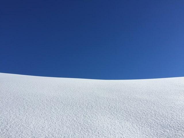 In der oberen Bildhälfte ist tiefblauer Himmel zu sehen. Unten ein unberührtes Schneefeld.