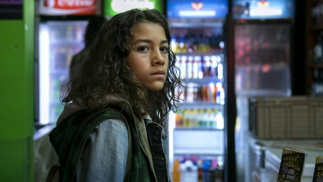 Ein Mädchen vor einem Getränkeautomaten