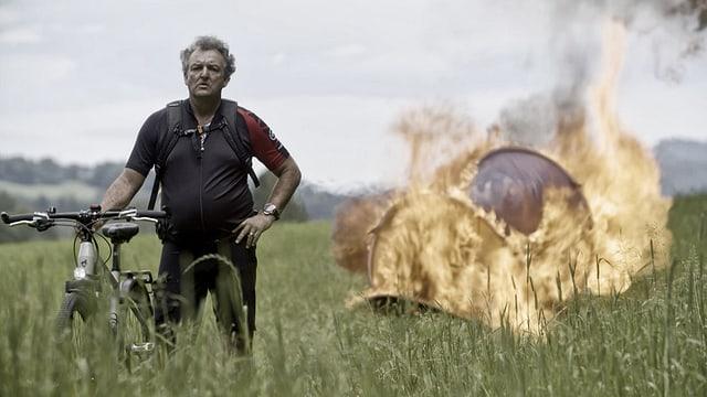 Marco Rima vor einem brennenden Zelt.