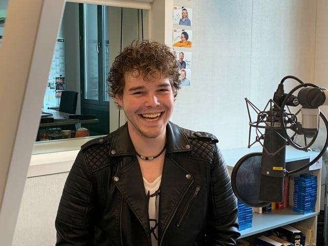 Junger Mann mit Lederjacke im Radiostudio.