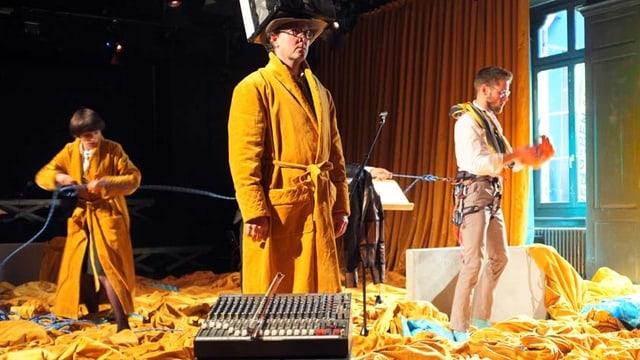 Drei Schauspieler, zwei davon in orangen Bademänteln, stehen auf der Bühne, die von orangem Stoff überschwemmt ist.