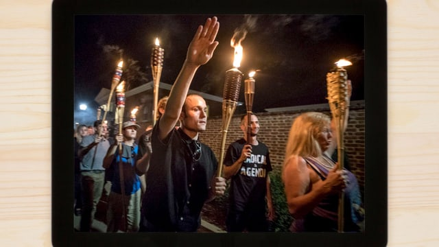 Menschen mit Fackeln. Ein Mann macht den Hitlergruss.