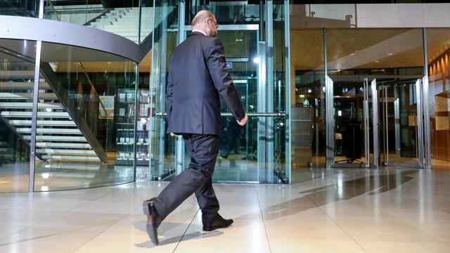 Rückenansicht von Schulz. Er geht einen Flur entlang.
