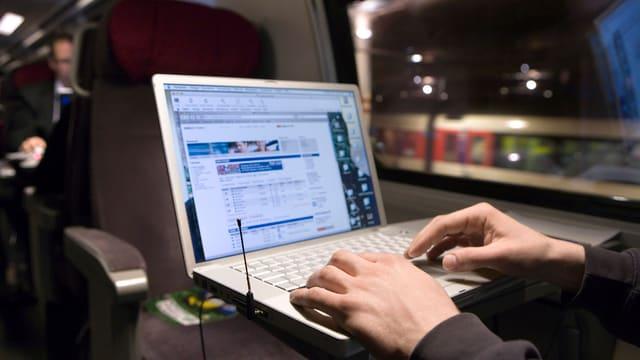 Das Bild zeigt einen Zugreisenden mit einem Laptop.
