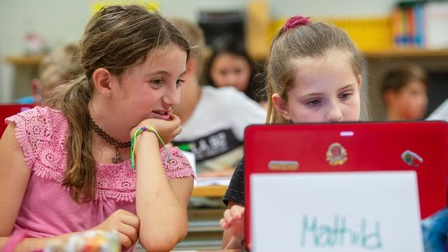 scolaras che lavuran durant l'instrucziun vid in laptop