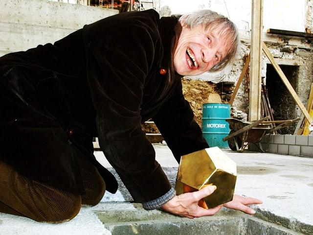 Dimitri kniet über einem Loch im Boden und hält einen goldenen Würfelbehälter.