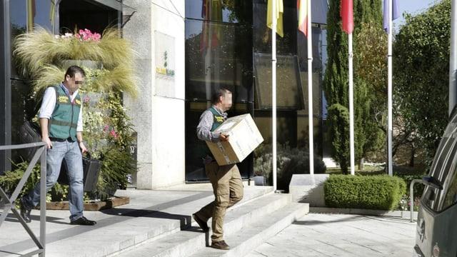 Ein Ermittler trägt einen Karton mit Dokumenten weg.