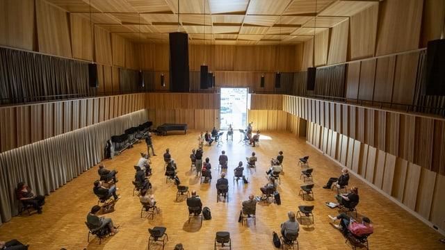 Konzertsaal aus dunklem Holz mit Stühlen in der Mitte
