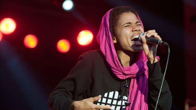 Eine Frau singt auf einer Bühne. Sie hat einen rosafarbenen Schal um den Kopf gelegt und singt mit weit geöffnetem Mund und geschlossenen Augen.