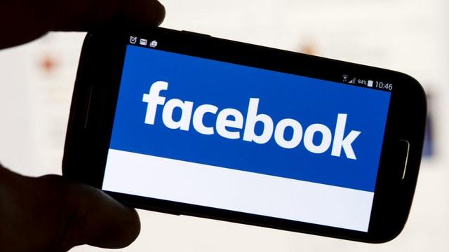 Eine Hand hält ein Smartphone, auf dessen Screen Facebook geschrieben steht.