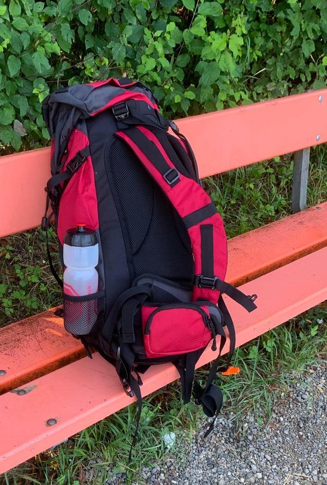 Roter Rucksack auf roter Sitzbank.