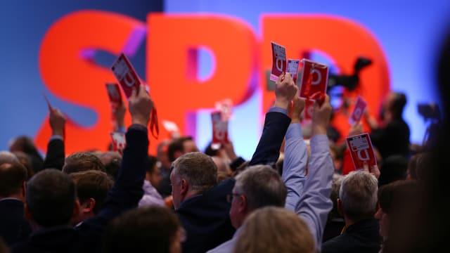 Rückenansicht von SPD-Delegierten mit hochgereckten Armen und Ausweisen in der Hand vor einem SPD-Logo.