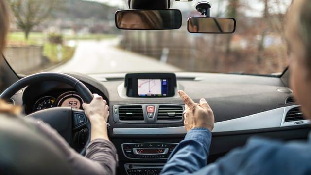 Zwei Menschen sitzen in einem Wagen, der rechts zeigt mit dem Finger, wo's lang geht.
