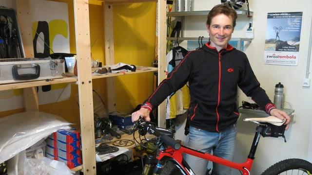 Lukas Stöckli steht mit seinem Bike im Velokeller.