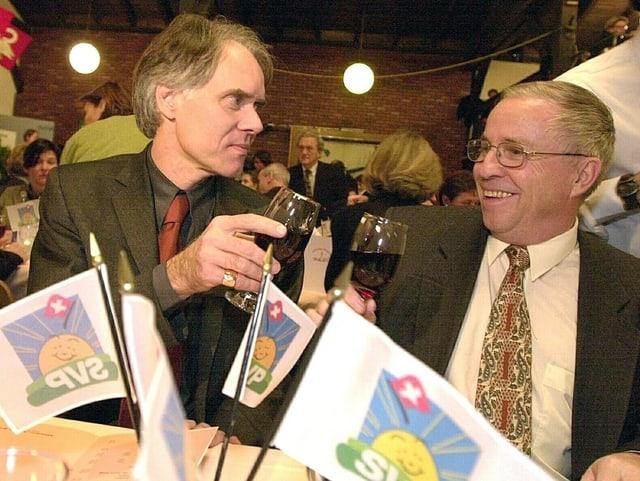 Die Politiker Moritz Leuenberger und Christoph Blocher stossen gemeinsam an