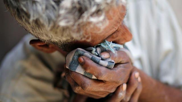 Ein Mann wischt sich mit einem Tuch die Tränen ab.