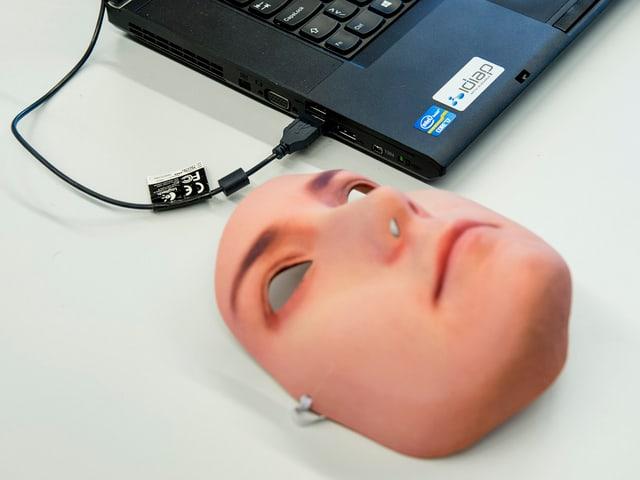 Eine Gesichtsmaske neben einem Computer.