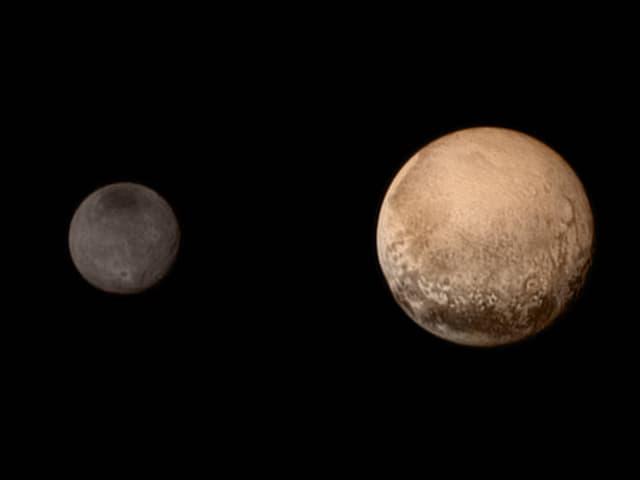 Im Vordergrund der bronzefarbene Zwergplanet Pluto, im Hintergrund, grau, Charon.