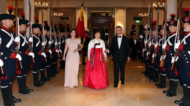 Bundespräsident Burkhalter und seine Ehefrau schreiten zusammen mit Präsidentin Park in ihrer Mitte eine historische Ehrengarde ab.