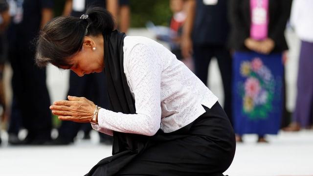 Aung Sang Suu Kyi kniet auf einem roten Teppich und hält die Hände zum Gebet verschränkt.
