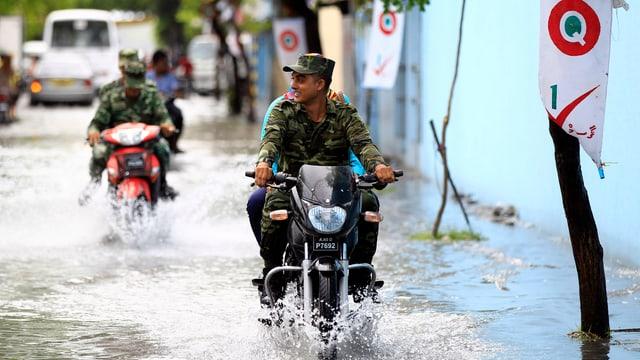 Soldaten fahren auf Motorrädern auf einer überfluteten Strasse in Male.