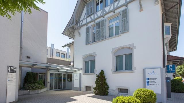 Weisses Haus mit Fachwerk Dach davor ein Schild mit Obach-Beschriftung