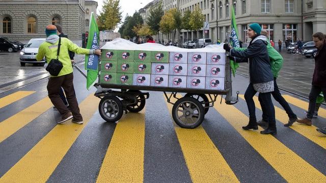 Unterstützer der Initiative «Zersiedelung stoppen» schieben einen Wagen mit Kisten.