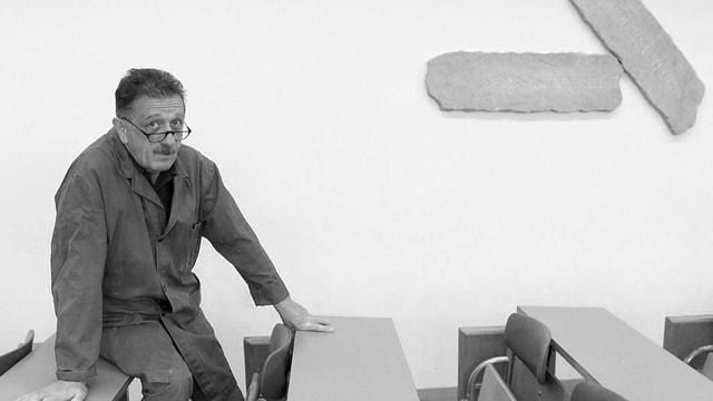 Carlo Lischetti sitzt auf einem Pult, an der Wand hängen zwei Holzstücke in länglicher Form.