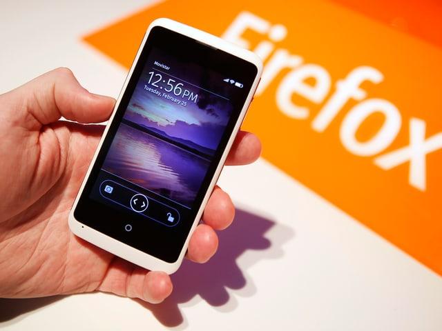Eine Hand hält ein Smartphone auf dem Mozillas Betriebssystem Firefox OS läuft.