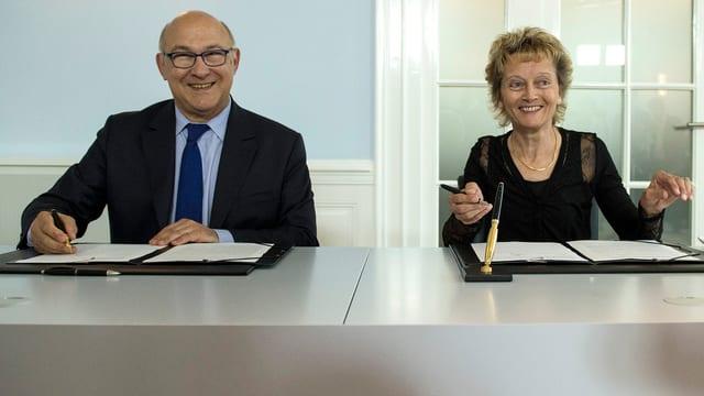 Finanzminister Michel Sapin und Bundesrätin Eveline Widmer-Schlumpf lachen bei der Vertragsunterzeichnung.