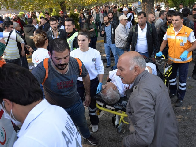 Helfer bringen einen Verletzten auf einer Bahre weg.